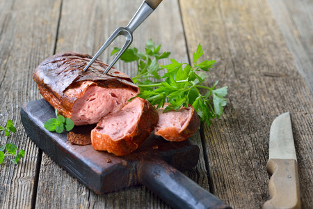 leberkaese: Traditional oven fresh Bavarian meat loaf on a wooden cutting board garnished with parsley
