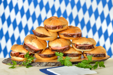 leberkaese: Traditional oven fresh Bavarian meat loaf on crisp rolls, the Bavarian flag in the background Stock Photo