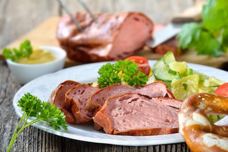 Porción del horno de pan de carne fresca bávaro con ensalada de patatas, pretzel y mostaza Foto de archivo