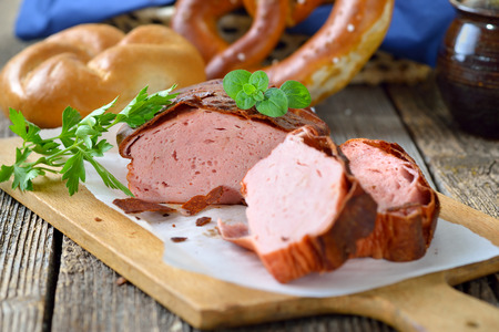 leberkaese: Traditional oven fresh Bavarian meat loaf with a crispy brown crust on a wooden cutting board garnished with parsley and oregano, a roll and a pretzel in the background in soft focus