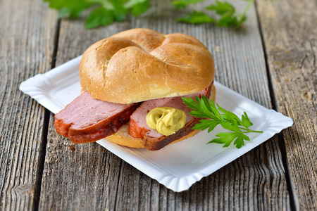 baked meat: Bavarian takeaway food: A roll with baked meat loaf and mustard on a paper plate Stock Photo