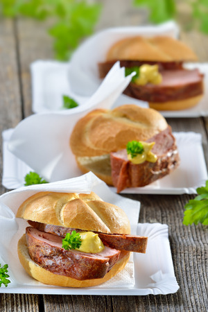 baked meat: Bavarian takeaway food: Three rolls with baked meat loaf and mustard on paper plates