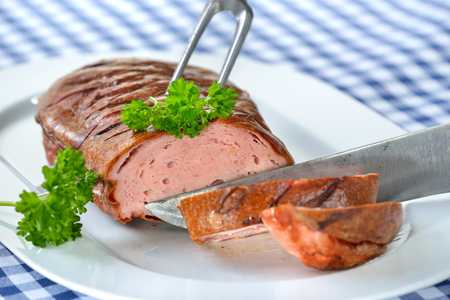sumptuous: Bavarian meat loaf on a white plate served on a table with a white and blue checkered tablecloth Stock Photo