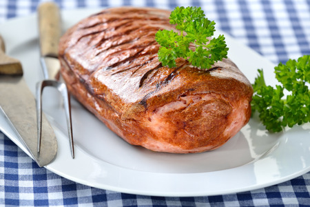 leberkaese: Bavarian meat loaf on a white plate served on a table with a white and blue checkered tablecloth Stock Photo