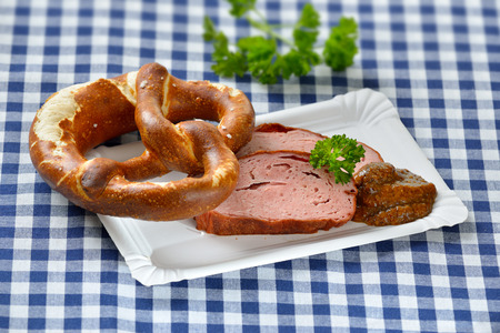leberkaese: Bavarian takeaway food: Slices of hot meatloaf with sweet mustard and a pretzel on a paper plate