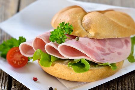 embutidos: Rollo crujiente con salchichas en rodajas ?? jamón en un plato de papel con una servilleta