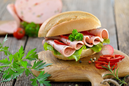 wooden board: Bun with sliced ??bell pepper sausage on a rustic wooden board