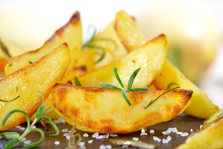 baked potato: Baked potato wedges with rosemary served on a shabby cutting board with potatoes in the background