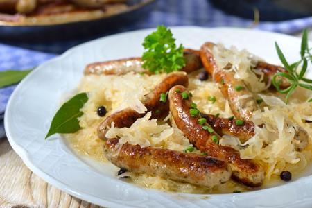Fried Bavarian sausages from Nuremberg served on sauerkraut sausages someother in the background Reklamní fotografie - 59406927