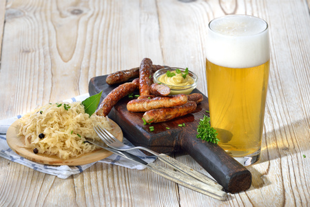 downloaded: Fried Bavarian sausages from Nuremberg served with Sauerkraut and a lager beer