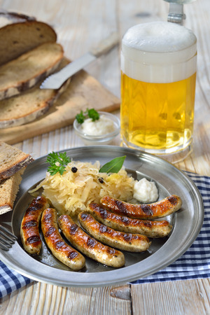 pewter: Bavarian beer garden meal - Fried sausages from Nuremberg with Sauerkraut and horseradish traditionally served on a pewter plate with hearty farmhouse bread and a tankard of cold lager beer Munich
