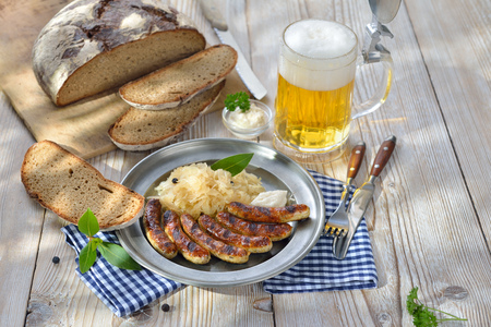 Bavarian beer garden meal - Fried sausages from Nuremberg with Sauerkraut and horseradish traditionally served on a pewter plate with hearty farmhouse bread and a tankard of cold lager beer Munich
