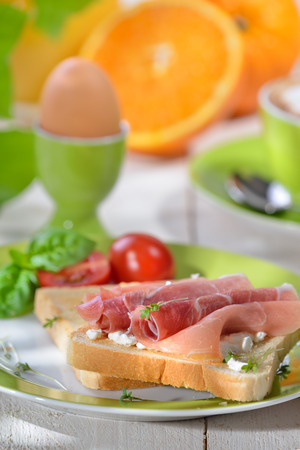 breakfast cup: Breakfast with ham toast, a boiled egg, orange juice and a cup of cappuccino