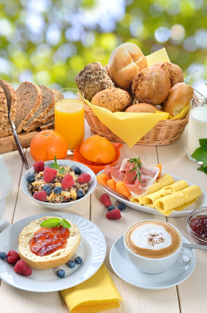 Outside served breakfast in summer with a cup of cappuccino and a large selection of food Reklamní fotografie - 61724051