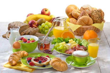 breakfast cup: Breakfast table with a cup of cappuccino and a large selection of food against a white background