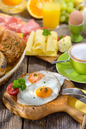 fried foods: Outside served luxuriant breakfast with fried eggs a wide selection of other foods