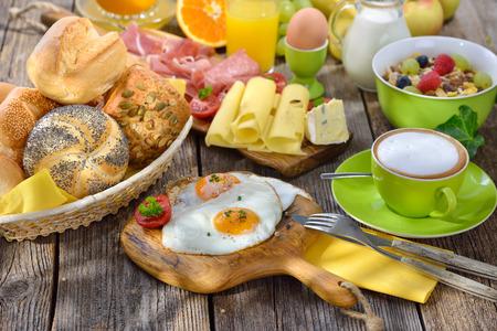 buns: Fuera sirve el desayuno con huevos fritos exuberante una amplia selección de otros alimentos Foto de archivo