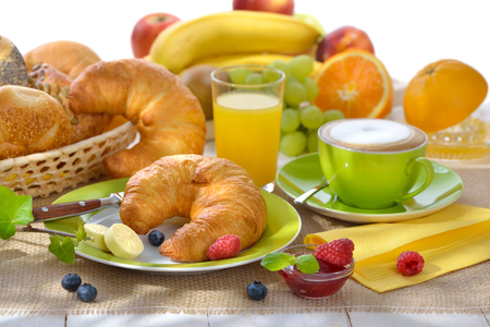 Breakfast table with a cup of cappuccino and fresh croissants with butter and jam against a white background
