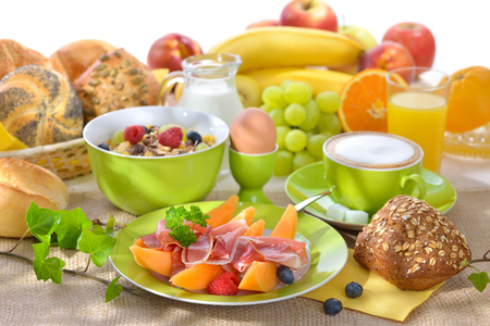 laid: Laid breakfast table with melon and ham against a white background