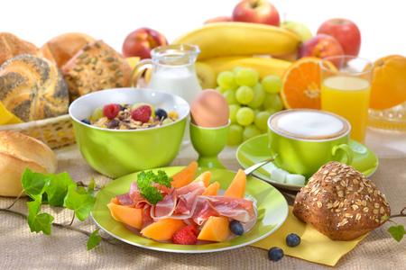 comida rica: Laid mesa del desayuno con melón y jamón sobre un fondo blanco