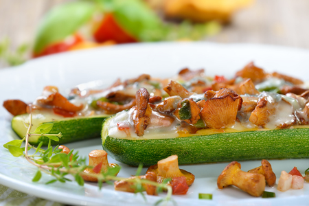 girolle: Zucchini halves stuffed with fresh chanterelles and topped with grated gorgonzola cheese Stock Photo
