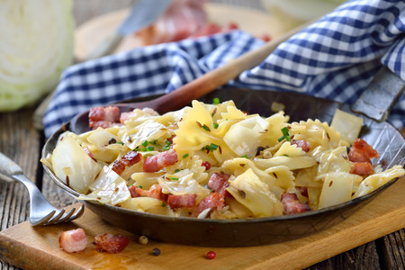 Pasta with fried white cabbage and bacon to Austrian specialty called Krautfleckerl, served in a iron frying pan