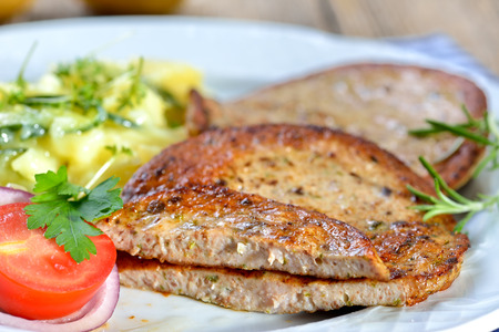 Bavarian food: Fried slices of sausage with pieces of pig spleen (so called Milzwurst) served with potato salad