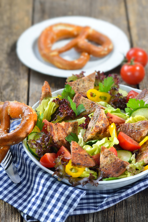 Bavarian salad: Pieces of fried sausage with pig spleen served on a colorful mixed salad