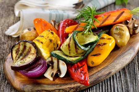 Cuisine végétalienne: Légumes mélangés grillés sur une planche à découper en bois Banque d'images - 62812594