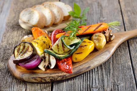 Vegan cuisine: Mixed grilled vegetables on a wooden cutting board served with Italian ciabatta bread