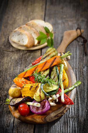 grilled vegetables: Vegan cuisine: Mixed grilled vegetables on a wooden cutting board served with Italian ciabatta bread