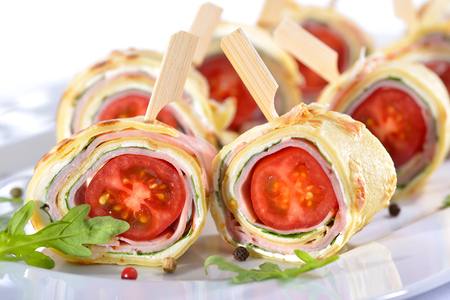 downloaded: Delicious finger food: Rolls of thin pancakes (crepes) with ham, cream cheese, rocket salad and cherry tomatoes Stock Photo
