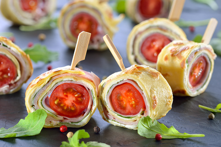 downloaded: Delicious finger food: Rolls of thin pancakes (crepes) with ham, cream cheese, rocket salad and cherry tomatoes served on a slate Stock Photo