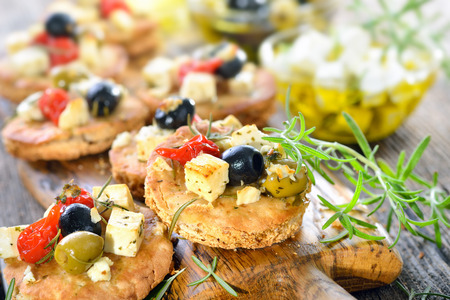 Warm Greek appetizers: Crispy baked pita bread with feta cheese, olives, peppers and herbs
