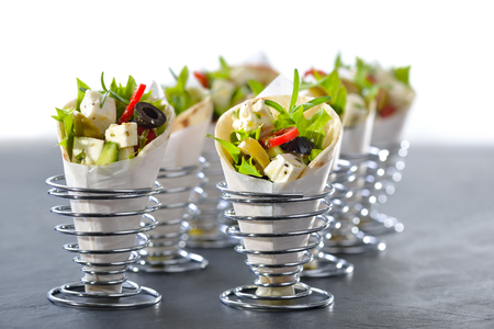 Mini tortillas stuffed with Greek farmers salad with feta cheese and olives, served in wire egg cups Reklamní fotografie - 63747885