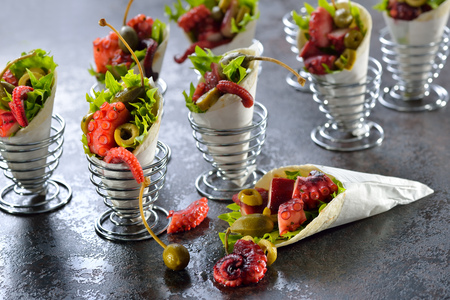 egg cups: Mini tortillas stuffed with octopus salad with olives and capers, served in wire egg cups