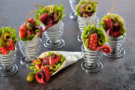 downloaded: Mini tortillas stuffed with octopus salad with olives and capers, served in wire egg cups