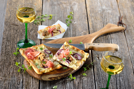Tarte Flambee from Alsace with sour cream, onions, mushrooms and serrano ham, served with local Alsatian wine Reklamní fotografie - 63747899