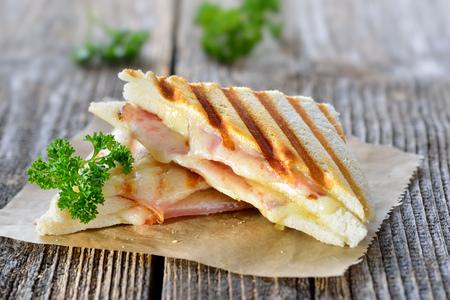 ハムとチーズのサンドイッチで押されたとトーストのダブル パニーニを木製のテーブルに紙の上提供しています