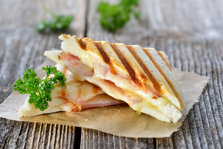 Pressed and toasted double panini with ham and cheese sandwich served on paper on a wooden table Foto de archivo