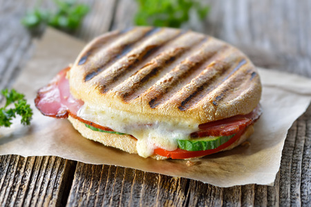Grilled and pressed panini with smoked ham, cheese, cucumber and tomato served on sandwich paper on a wooden table