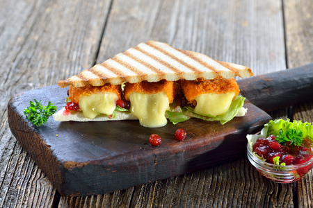 Toasted panini triangles with breaded camembert cheese mini loaves, cranberries and iceberg lettuce served on a wooden cutting board
