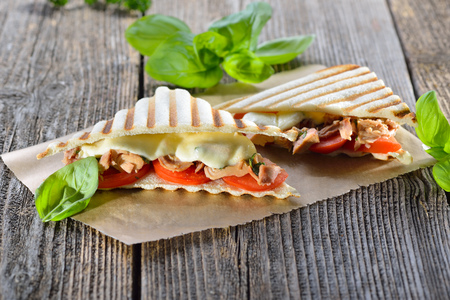 Toasted panini with tuna fish, tomatoes, melted mozzarella and fresh basil served on sandwich paper on a wooden table