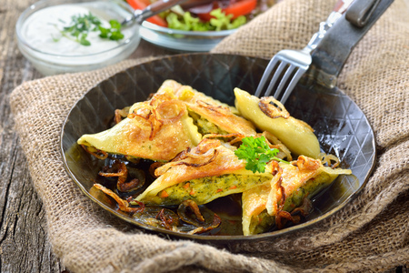 Fried Swabian ravioli (so called dumplings) with vegetable filling served with side salad and creamy herb cheese