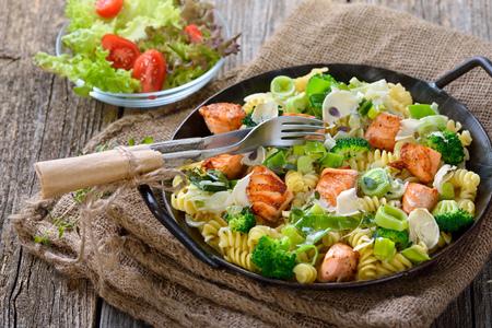 Italiaanse pasta met gebakken stukken zalmfilet, mierikswortel en een saus van room en prei geserveerd in een ijzeren koekenpan met een salade op de achtergrond