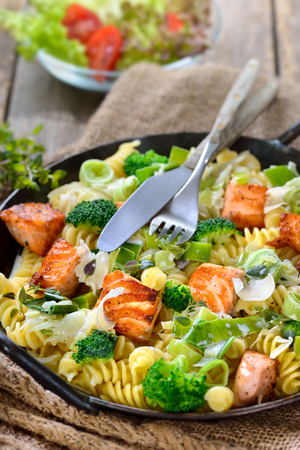 downloaded: Italian pasta with fried cuts of salmon fillet, horseradish and a sauce of cream and leek served in a iron frying pan with a side salad in the background Stock Photo