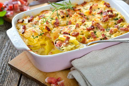 Hearty potato gratin with parmesan cheese, cream and delicious cured bacon from South Tyrol freshly served from the oven