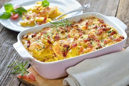 Gratin de pommes de terre copieux avec du fromage parmesan, crème et délicieux cured bacon du Tyrol du Sud fraîchement servi du four Banque d'images - 67175208