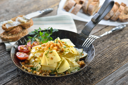 Austrian cuisine: Roasted square shaped pasta with bacon cracklings (so-called Grammelfleckerl) served in on iron frying pan, rye bread with crackling fat in the background Stock Photo