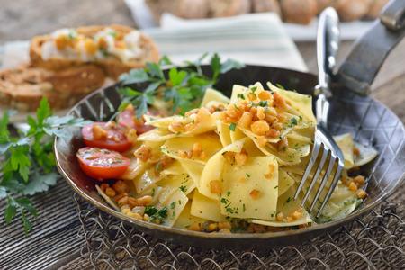 pancetta cubetti: cucina austriaca: arrosto quadrato di pasta a forma di ciccioli pancetta (i cosiddetti 'Grammelfleckerl') servito in su padella di ferro, pane di segale con scoppiettante grasso in background